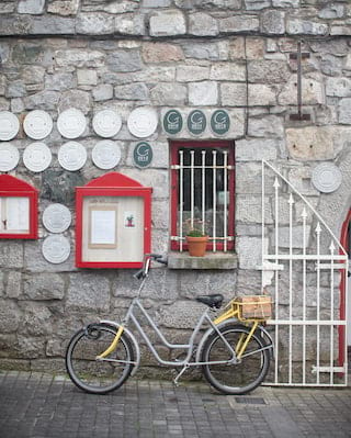 Close-up of a bicycle parked against a granite stone wall lined with award plaques
