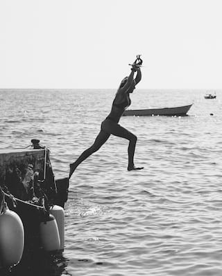 A black and white photo of a woman jumping into the sea