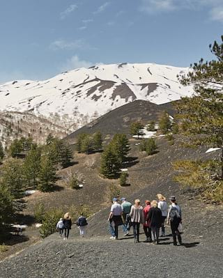 Tourists on the slopes of Mount Etna with the snow-capped peak in the distance