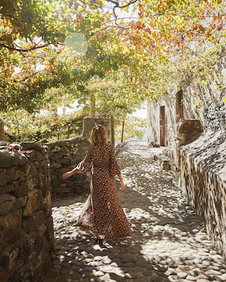 Lady in a summer dress walking along a cobbled path under the shade of trees