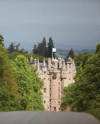 The pink granite stone of Glamis Castle rising at the end of a long driveway