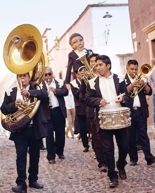 Mexican band parading along cobblestone streets with drums and a trombone