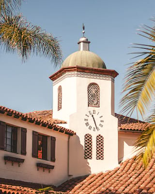 White courthouse building, with terracotta tile roof and clock spire
