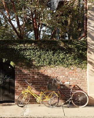 Bicycles placed against a brick wall next to an arched garden gate