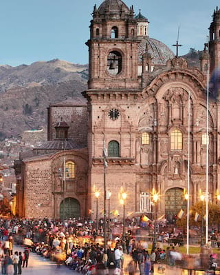 Ornate lamplit facade of a Spanish-colonial church surrounded by crowds at sunset