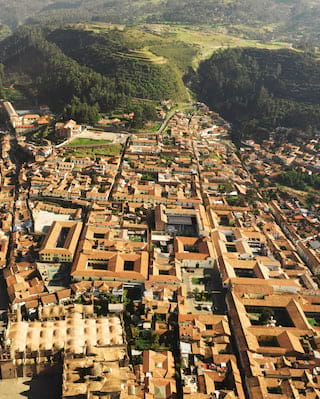 Aerial view of Cusco city and green hills in the distance