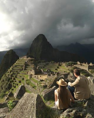 Casal sentado em uma rocha com vista para a cidadela Inca de Machu Picchu