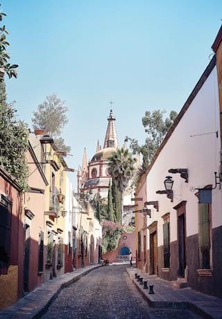 Fileira de casas coloniais espanholas em tons pastéis em uma rua de paralelepípedos