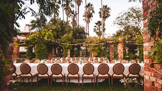Banquet tables in a courtyard surrounded by foliage and fairy lights