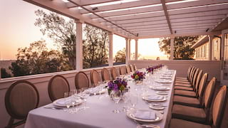 Banquet table on a shaded terrace at sunset with flower centerpieces