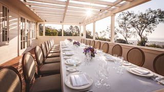 Banquet table on a shaded terrace at sunset, set for a corporate event