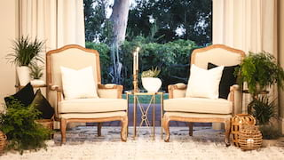 Two pale-hued armchairs side-by-side with patio and gardens beyond