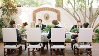 Wedding guests around a table on an outdoor patio surrounded by gardens