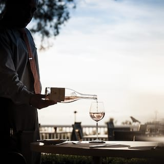 Waiter pouring white wine into a glass with view of blue skies beyond