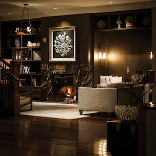 Guest lobby in low light with a fireplace and dark paneled walls