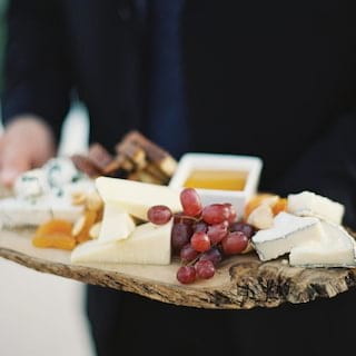 Close-up of a cheese board piled with grapes, apricots and cheeses