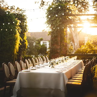 Long banquet table set for a party in hotel gardens at sunset
