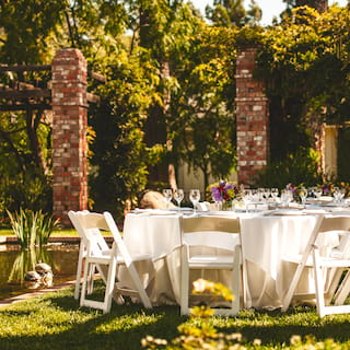 Circular tables set for a party in a sunny courtyard with a lily pond