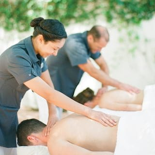 Couple on spa tables both receiving back massages by spa therapists