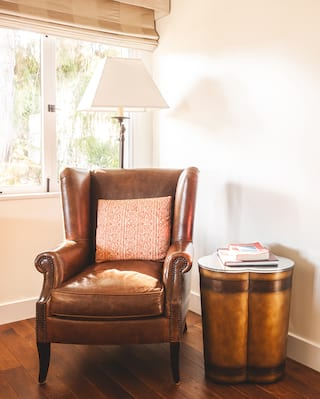 Leather armchair next to window with a polished wood side-table