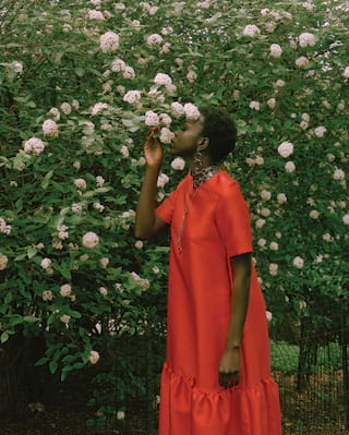 Lady in a red dress smelling flowers