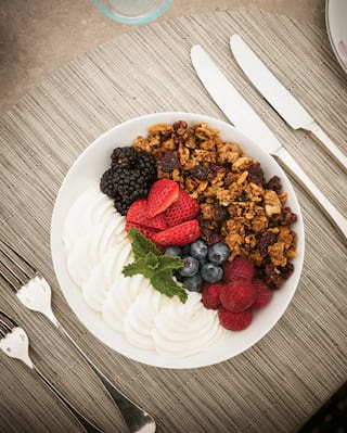 Granola, berries and yogurt in a circular bowl with a mint garnish