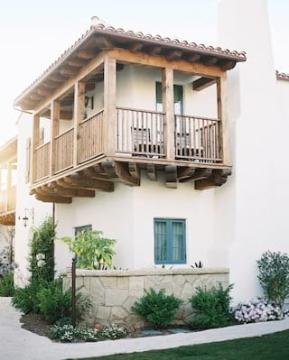 Wooden Spanish-style corner balcony with a terracotta tile roof