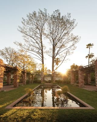 Rectangular lily pond surrounded by red-brick pergolas at sunset