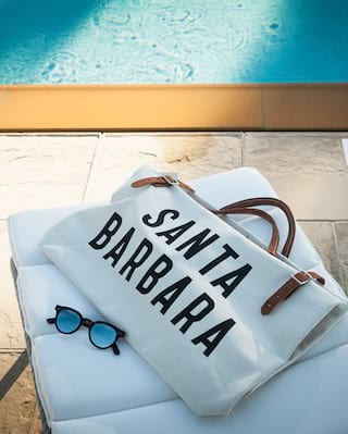 Poolside sunbed with sunglasses and tote bag placed on top