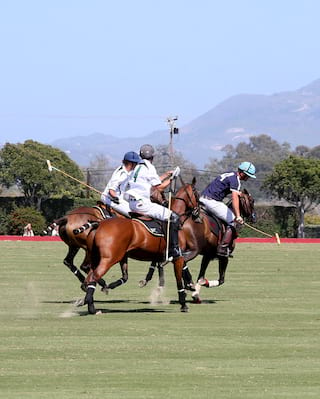 Three polo players on polo green with Santa Barbara hills in the background