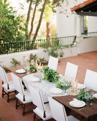 Wedding banquet table on a terrace, with candles and leafy centerpieces