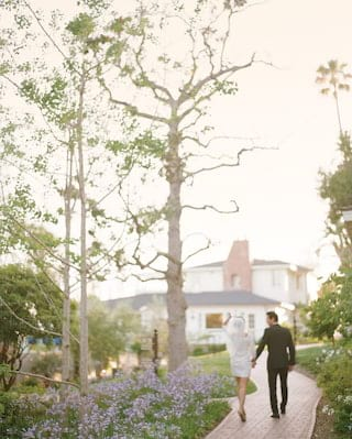 Bride and groom strolling along a red-brick path among hotel gardens