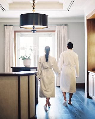 Couple hand-in-hand walking away from the camera in spa robes