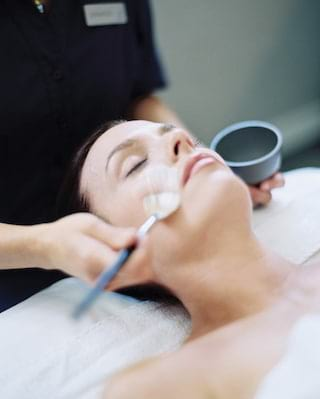 Close-up of a woman with closed eyes receiving a spa facial treatment