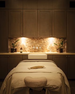 A spa treatment room in low light with spa table in the centre