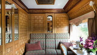Ornate wood-panelled train cabin with banquette seating and writing desk