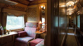 View of a lamplit train cabin in a corridor with gleaming French-polished panels