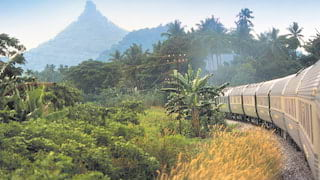 Train carriages curving through a jungle landscape with mountains beyond