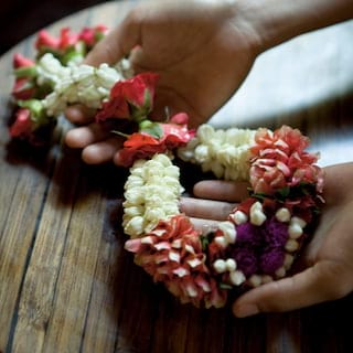 Close-up of two hands holding a sash made of real flowers