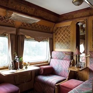 Train cabin with two picture windows, banquette seating and ornate marquetry