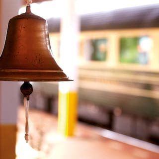 Close-up of a copper bell with train carriages in the background