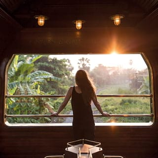 Lady looking out of an open-air train observation carriage at the sunrise beyond