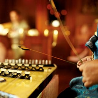 Close-up of hands plucking a traditional Thai khim string instrument