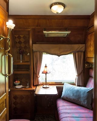 Train carriage with a blush coloured lampshade and ornate checkerboard marquetry