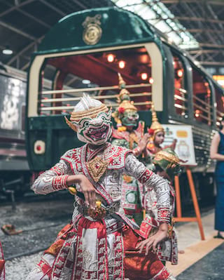Traditional Thai dragon dancers outside a luxury train carriage