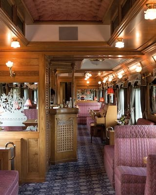 Cherry-wood panelled train bar car with mauve oriental soft furnishings