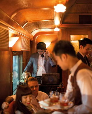 DJ mixing tracks in a wood-panelled train carriage filled with guests