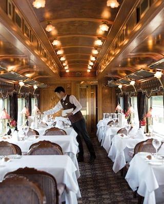 Waiter setting tables in an elegant lamplit restaurant dining car