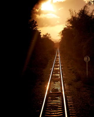 Sunlight catching on metal train tracks that stretch into the distance