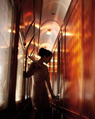 Silhouette of a lady in an evening gown in an ornate wood-panelled train corridor